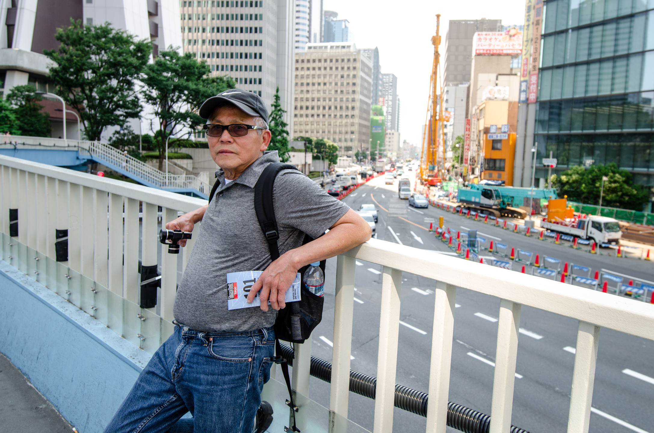 Sonny Tat relaxes along a bridge walkway railing in Tokyo Japan