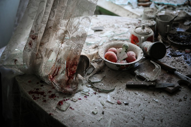 The photograph shows a table with uneaten eggs, a cold teapot, shattered glass and a blood-stained curtain. It was taken in Donetsk, Ukraine. It could have been taken anywhere experiencing the ravages of war.
