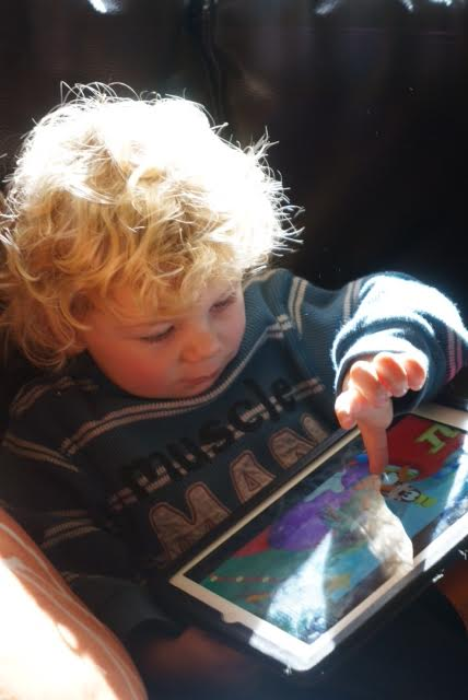 Grandson Hudson deftly manipulates an iPad, almost as if it is an extension of hand.