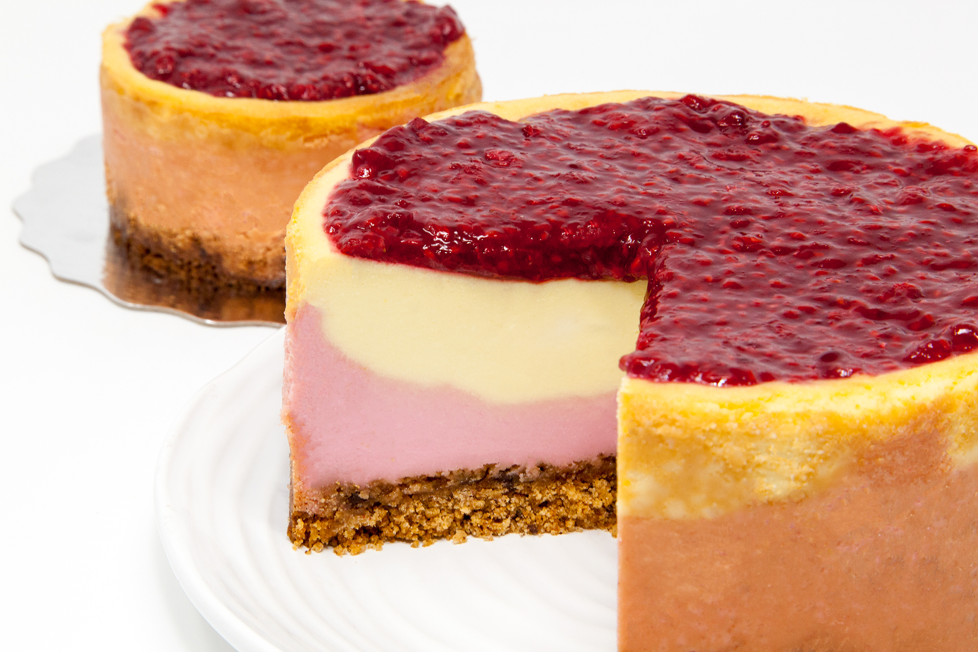 Raspberry Lemon Cheesecake with Double Thick Cookie Crumb Base  - Available in two sizes.