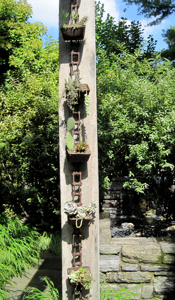 Last but not least, a chain of small succulent pots adorns a rustic column.