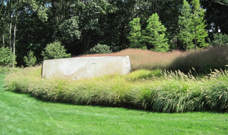 Ornamental grasses surround a stone sculpture.