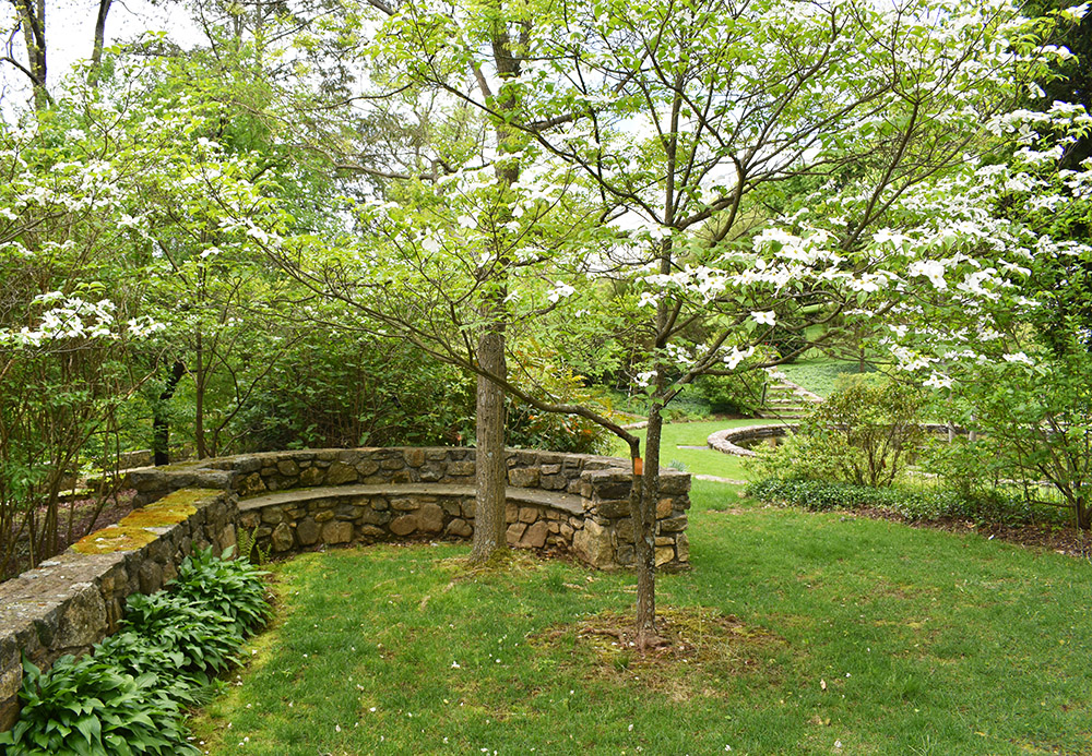 A semi-circular stone bench is built into the stone wall and repeats the circle motif.