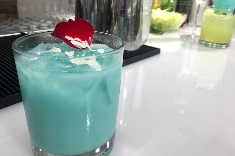 Blue Coco Colada - fresh lime juice, pineapple, Thai coconut water, blue spirulina, coconut flake & rose petal garnish