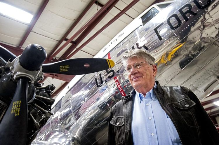 """In this March 7, 2016 photo, Karl Stoltzfus, Dynamic Aviation founder and chairman, poses for a photo with his restored DC-3, Miss Virginia, undergoing maintenance inside one of his company's hangars in Bridgewater, Va. Stoltzfus has purchased the plane known as """"Air Force One,"""" an aircraft that shuttled President Dwight Eisenhower around the globe, for a bit less than the $1.5 million asking price. (Daniel Lin/Daily News-Record via AP)"""