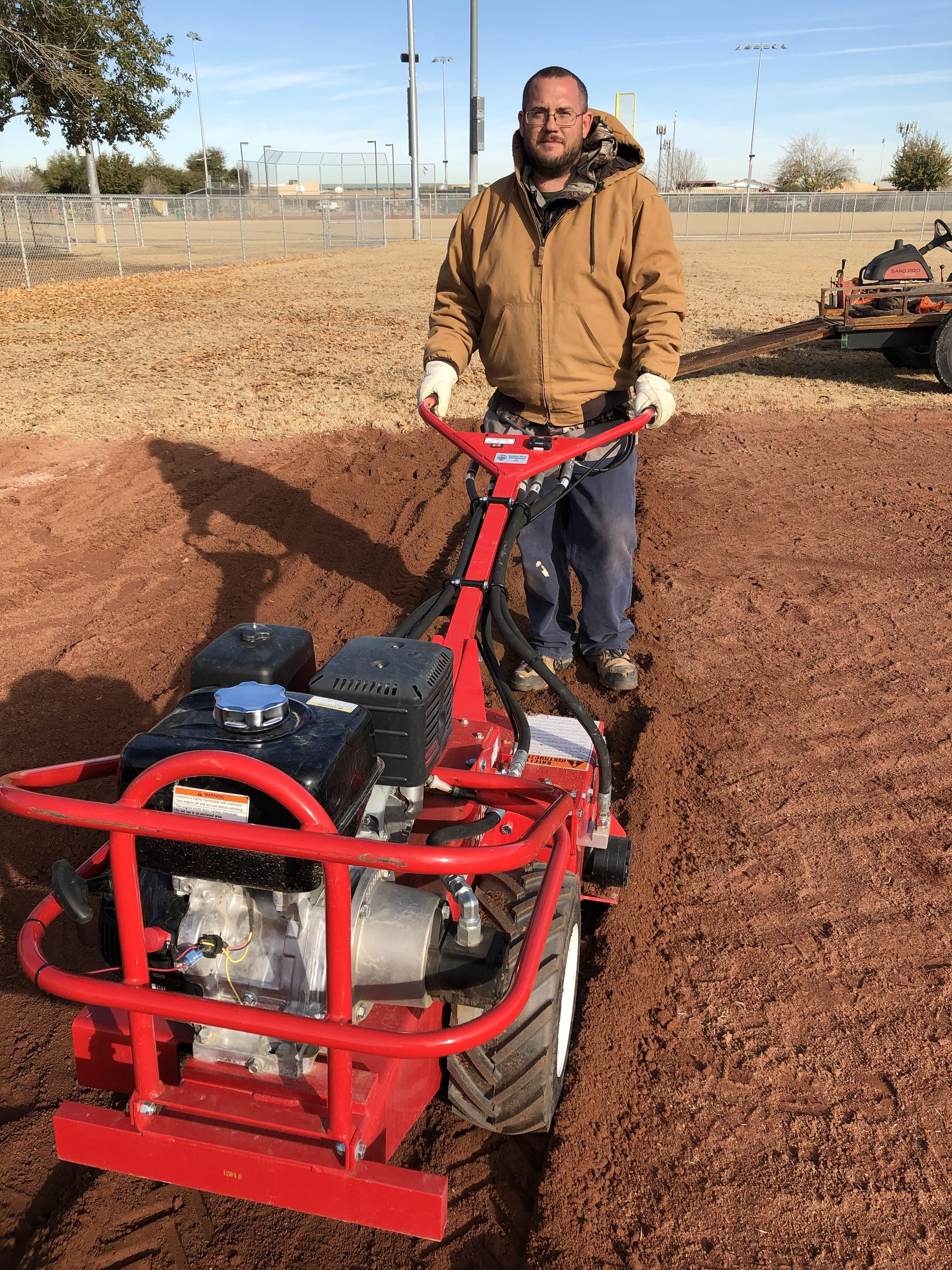 The rototiller breaks up the infield clay so that it may be redistributed and leveled.