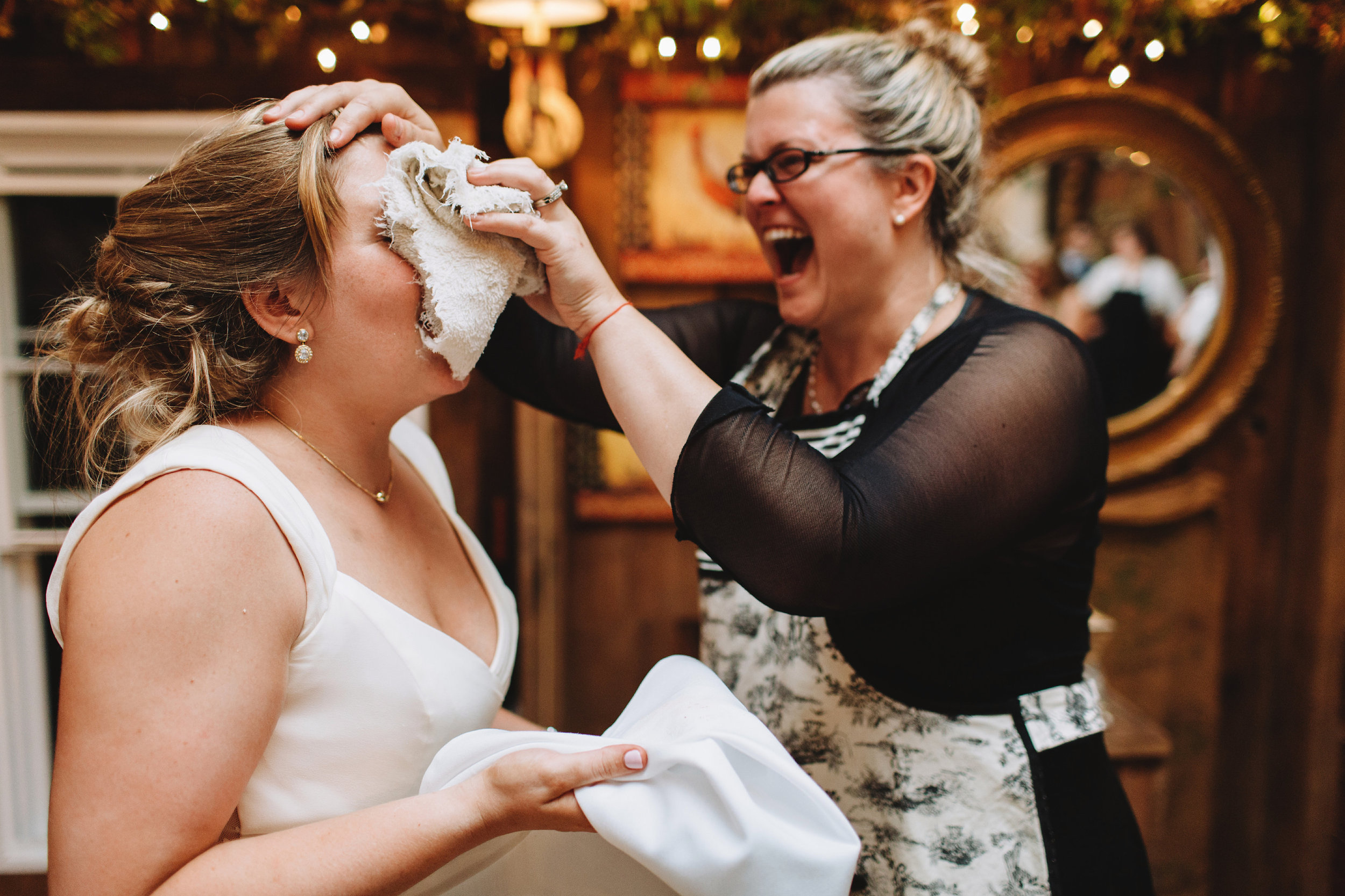Chanteclaire Owner Leigh Clarke helps a bride clean up after her new husband was enthusiastic with the wedding cake  Photo credit: With Love & Embers Photography