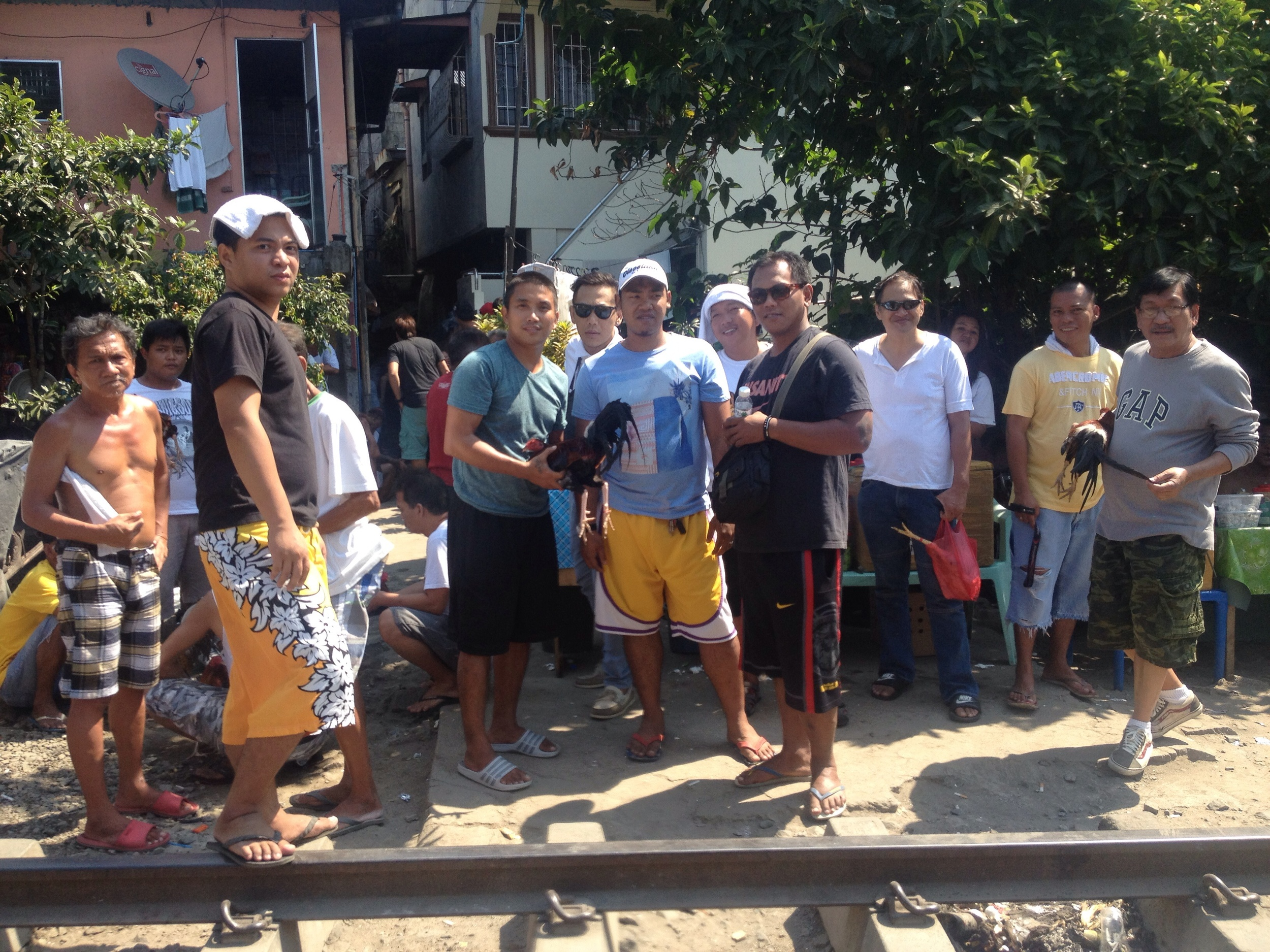On a Sunday along the train tracks in Navotas, men congregate from surrounding neighborhoods for an informal cockfight, locally called tupada.