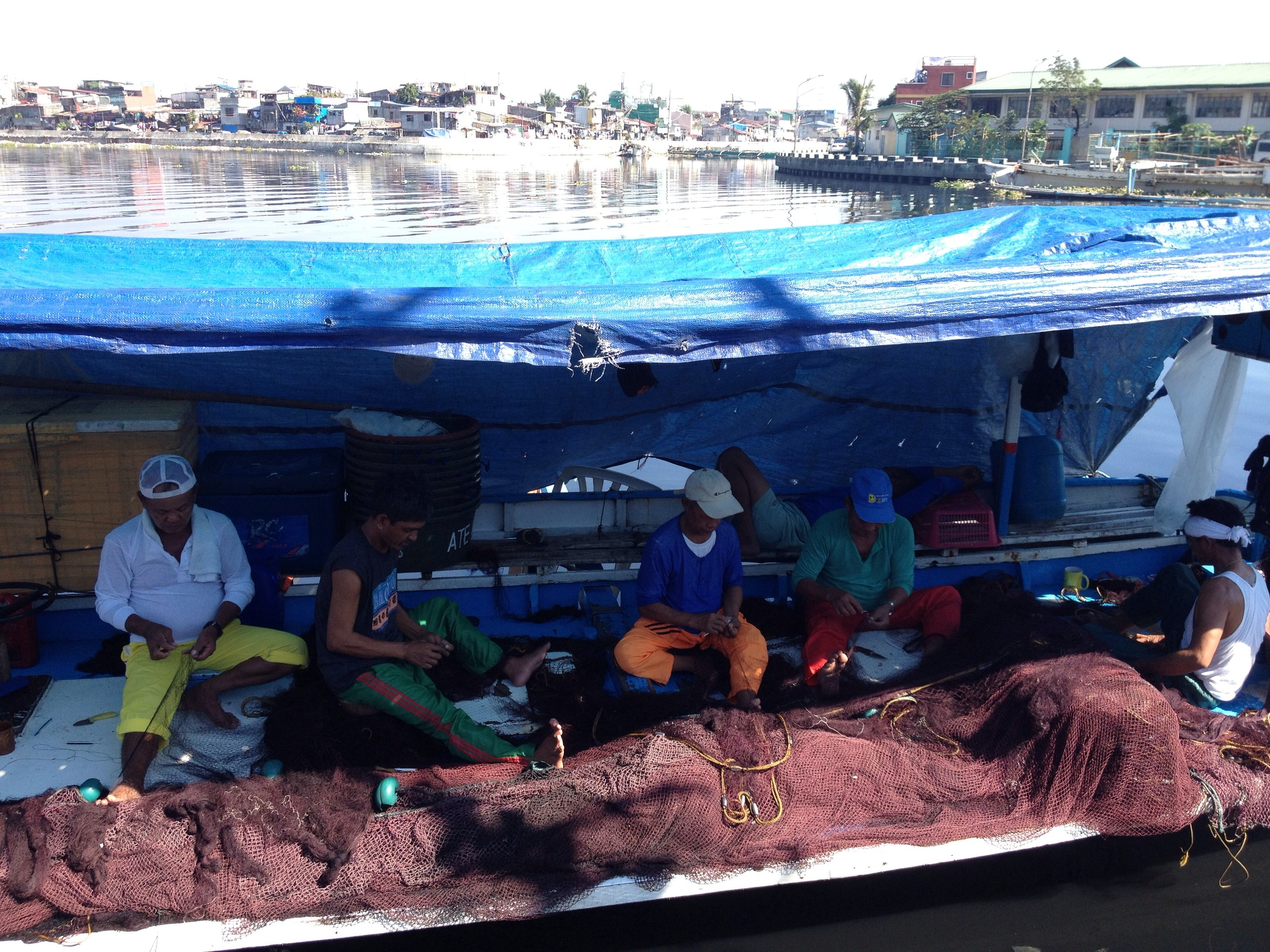 Fishermen repair nets on a hot afternoon along the Navotas River.