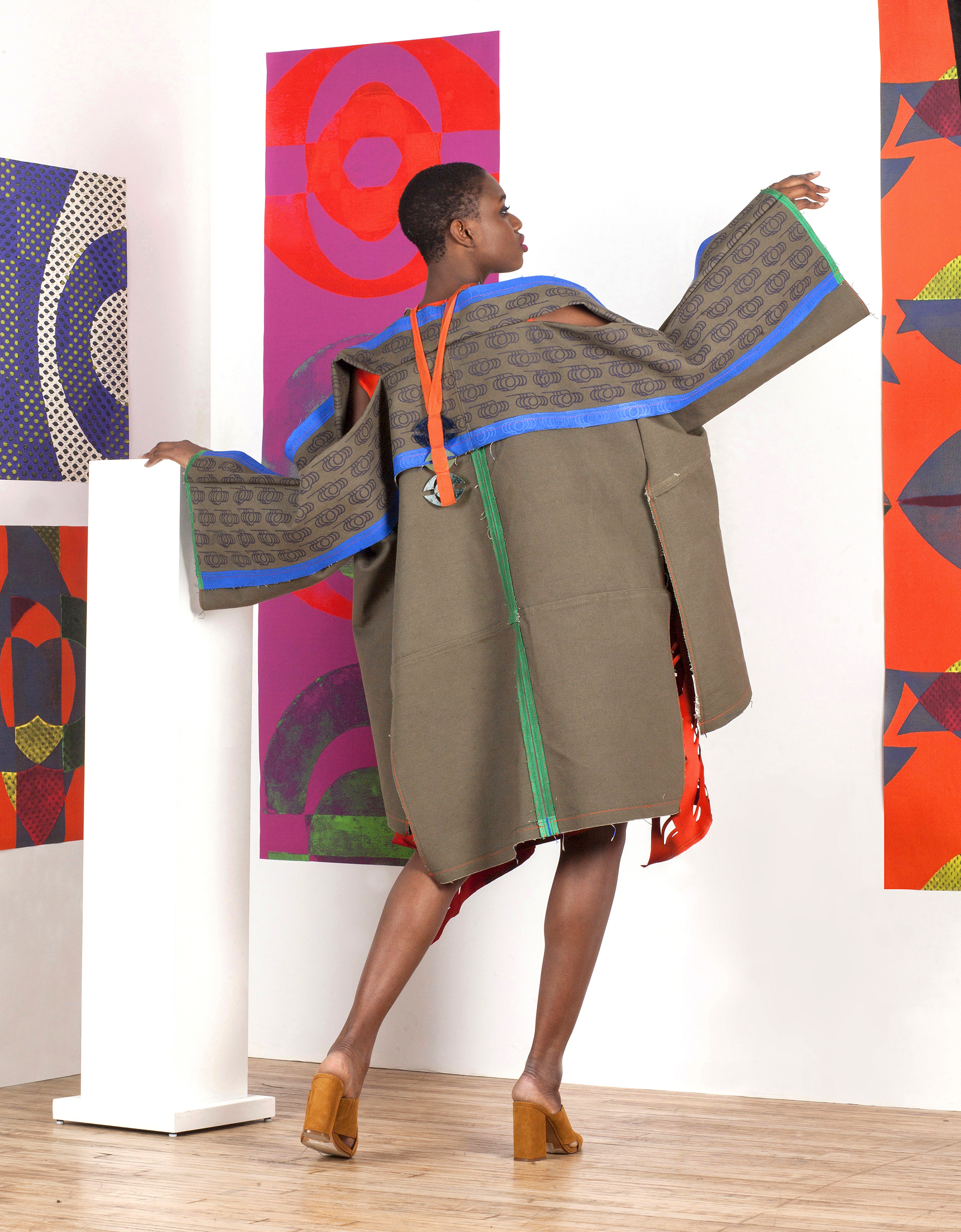Canvas Screen Printed and Edge Painted Extended Seam Allowance Jacket made from Vintage Army Duffle Bags.   Underneath is the Block Printed and Laser Cut Orange Double Faced Poly Satin Dress. Laser Cut Earrings.