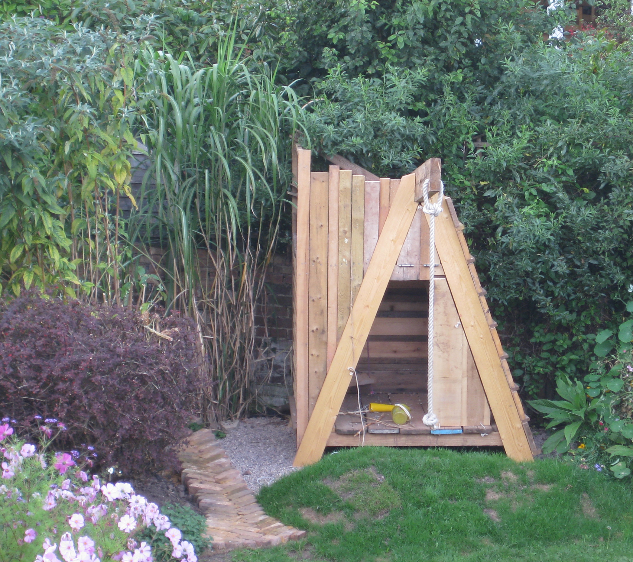 Childrens garden play structure, climbing frame, swing, fort and inner room with drawbridge.
