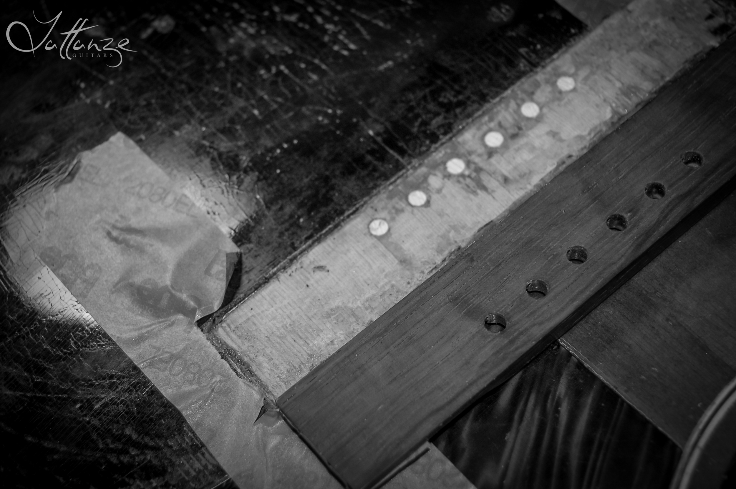 Tracing the oversized bridge onto the guitar and scoring to remove the finish.
