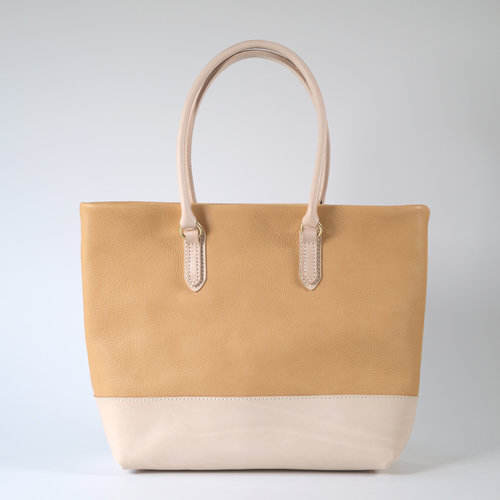 Tote Bag Horizontal - $440.00   Available in - Natural and Black  A luxury combination of milled and smooth grain vegetable tanned leathers, providing the perfect balance for this tote bag. This natural, un-dyed leather has a life of its own, starting as light beige in colour it changes through to a light tan before turning to dark tan. This can often take several years depending on sun exposure and naturally occurring oils in the environment. Featuring rounded handles for comfort and solid brass hardware. Made from vegetable tanned bovine leather, created by artisan tanners in Tuscany. The straps feature a smooth traditional vegetable tanned finish and the body is dry milled to produce a naturally occurring pebbled surface. The tote bag is fully lined with a natural cream coloured light weight canvas in 100% cotton. It has a double leather trimmed phone sized pocket and a small zip pocket. It will fit all your A4 sized objects. The Tote Bag Horizontal is handcrafted in Melbourne by Japanese trained leather artist, Sarah.   DIMENSIONS:  40cm x 10cm x 35cm (LWH)