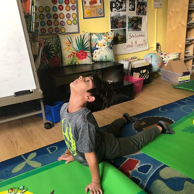 """Trey demonstrating bhujangasana (cobra) @holahoboken ,balancing a stone on his """"third eye"""" with intense focus. """"Patience"""" is the the theme for the 500plus students following The HudsonSeed curriculum this week. Join the movement and have your local school call us!!! @christafaro #choosejoy #weareinthistogether❤️"""
