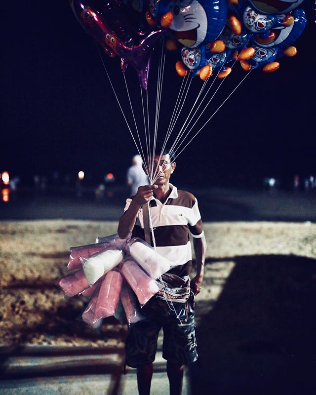 There is something interesting to me about this photo. He seems to be hiding behind his balloons. He also is looking directly at me.  I originally was disappointed about the man In white behind his head but it it does bring him out of the background and adds dimension and depth visually. One of my favorite photos from this trip.  #portraits #portrait #portraits_ig #pixel_ig #portraiture #expofilm3k #portrait_perfection #portraitstyles_gf #snowisblack #portraits_universe #featurepalette #bleachmyfilm #portraitmood #featurepalette #rsa_portraits #makeportraits #profile_vision #top_portraits #life_portraits #postthepeople #quietthechaos #2instagood #way2ill #justgoshoot #artofvisuals #l0tsabraids #ftwotw #igPodium_portraits #ftmedd #portraitphotography