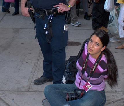 NYPD-credentialed photojournalist Julia Xanthos, wearing a 2007 NYPD-issued press credential along with a camera, under arrest by the NYPD for doing her job.