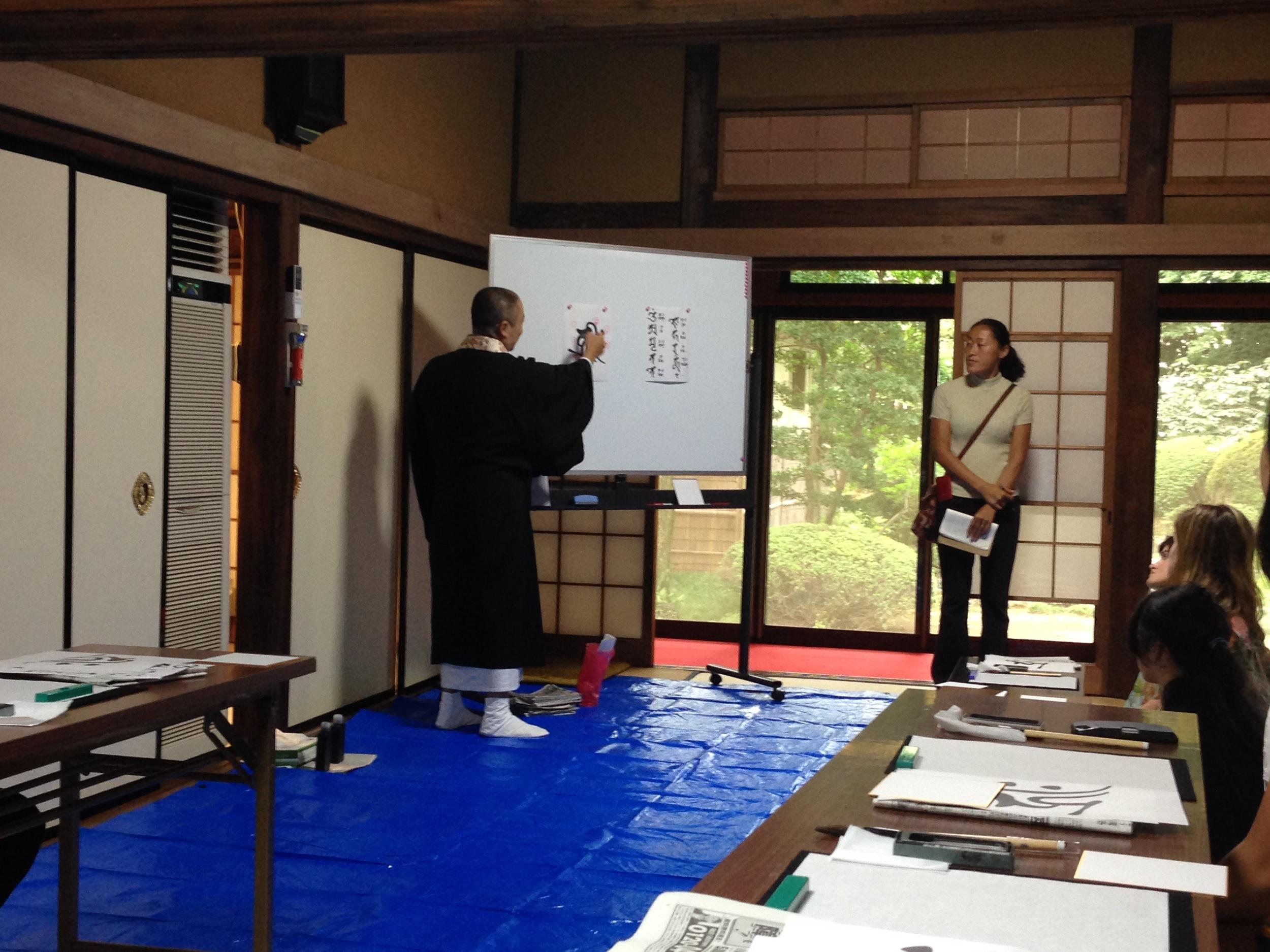 Teaching us calligraphy.