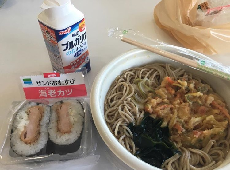 A lunch I bought a few months ago from a convenience store on my university's campus. From left to right:  ebi katsu omusubi  (shrimp fry rice-ball sandwich),  Burugaria  (Bulgarian yogurt drink), and  tanuki soba  (soba noodles with broth and deep-fried tempura bits). It all cost me about 5 dollars... disposable wooden chopsticks free of charge.