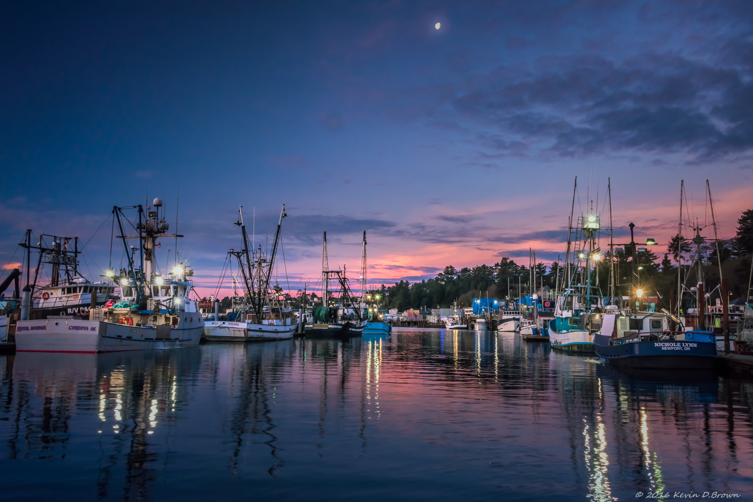 The moon falling in the sky as the sun begins to rise on Yaquina Bay in Newport, Oregon