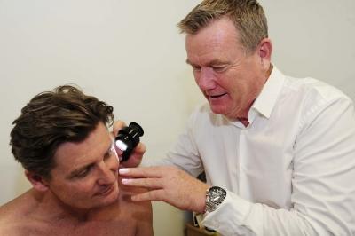 Dr Chris Boberg using a dermosocope to check moles
