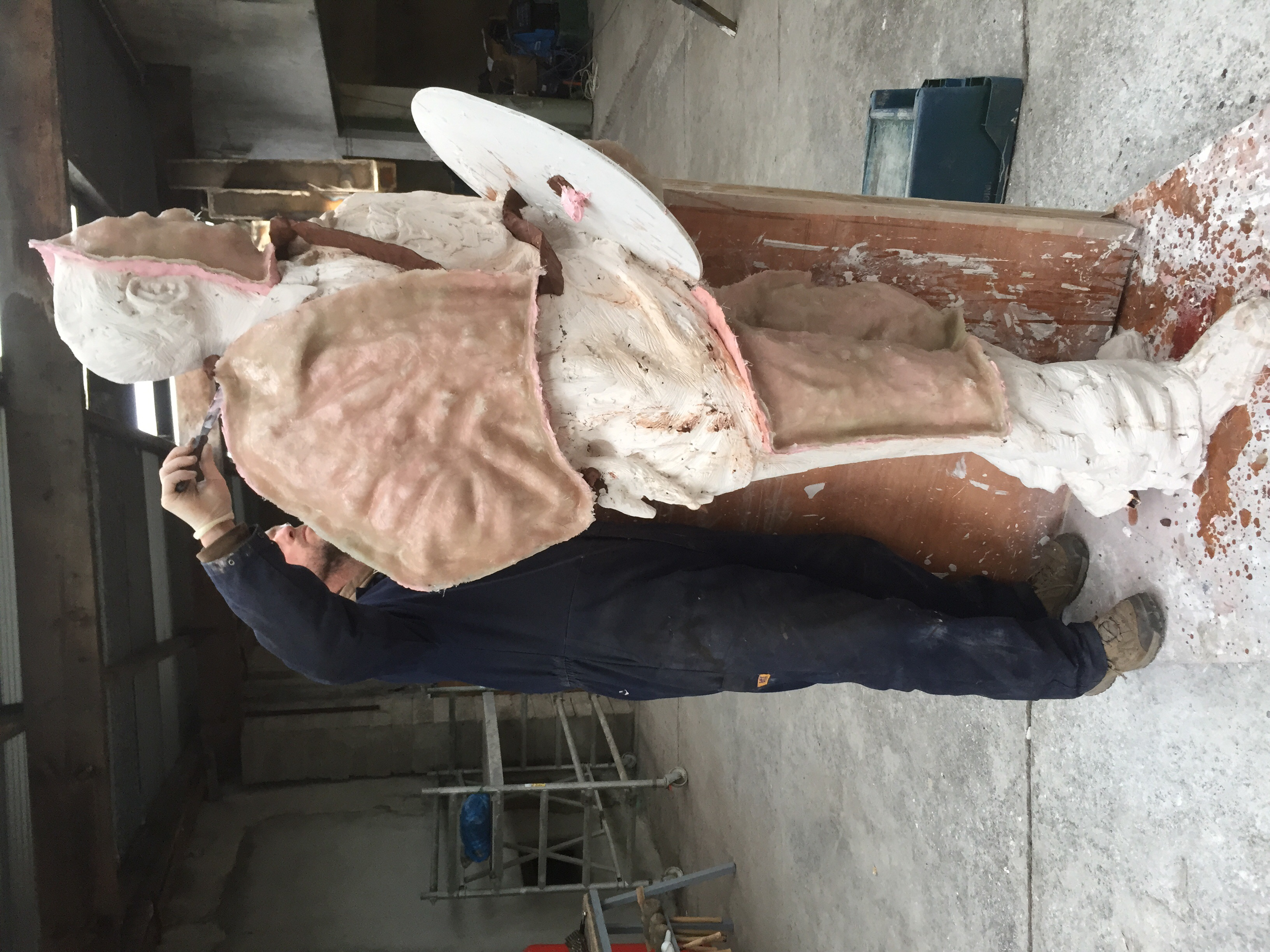 Taking the silicon mould of the plaster original: the pink silicon is towelled on before the resin and fibreglass support form