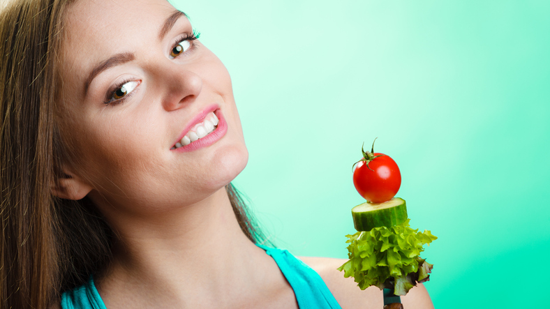 Healthy eating and diet concept. Happy young woman holding vegetables on blue background. Studio shot.