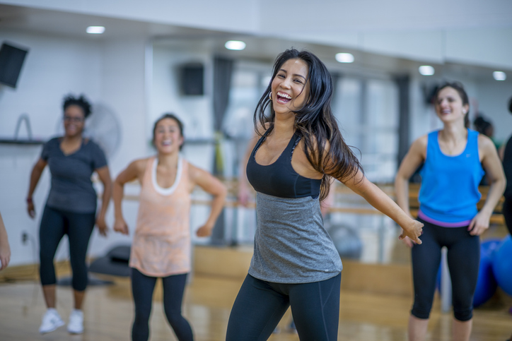 A multi-ethnic group of adult women are dancing in a fitness studio. They are wearing athletic clothes. An Ethnic woman is smiling while dancing in the foreground.