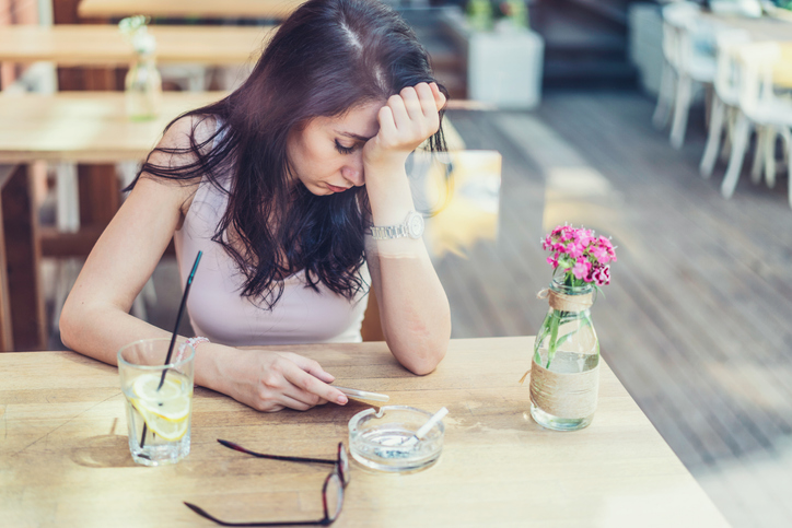 Portrait of brunette young woman sitting alone at the café, smoking cigarette and texting on her phone