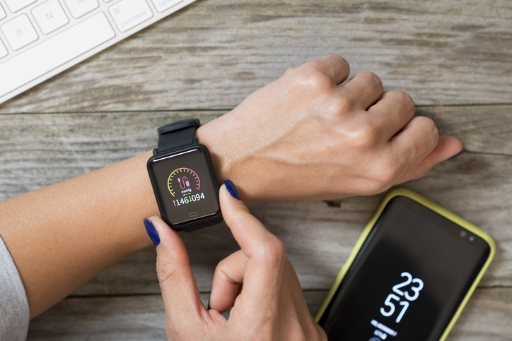 Woman measuring blood pressure with modern smart watch against wooden table