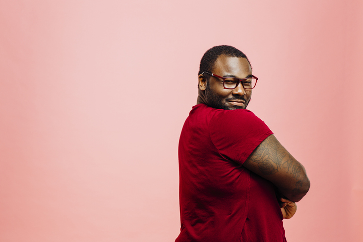 Portrait of a plus size man in red shirt and glasses looking back at camera, isolated on pink background