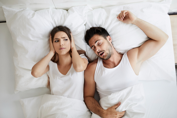 Stressed young woman covering her ears because her husband is snoring