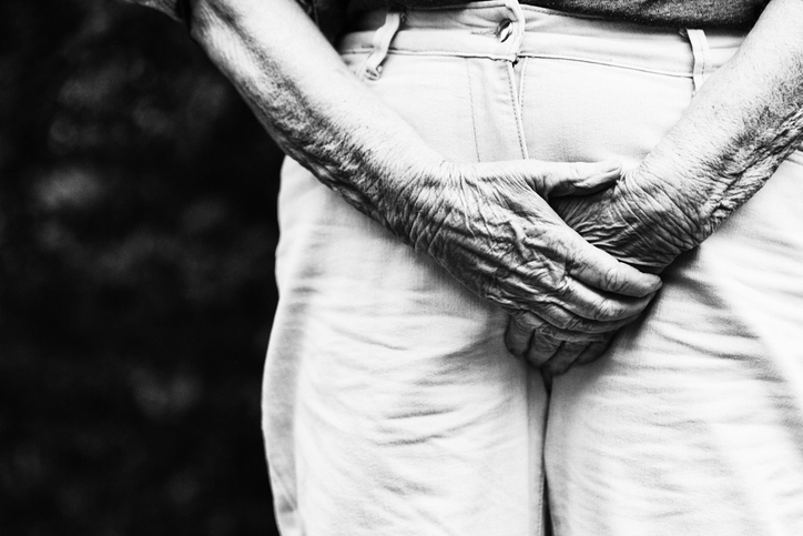 A senior woman's hands grab the front of her trousers in an effort to prevent a leak due to incontinence.