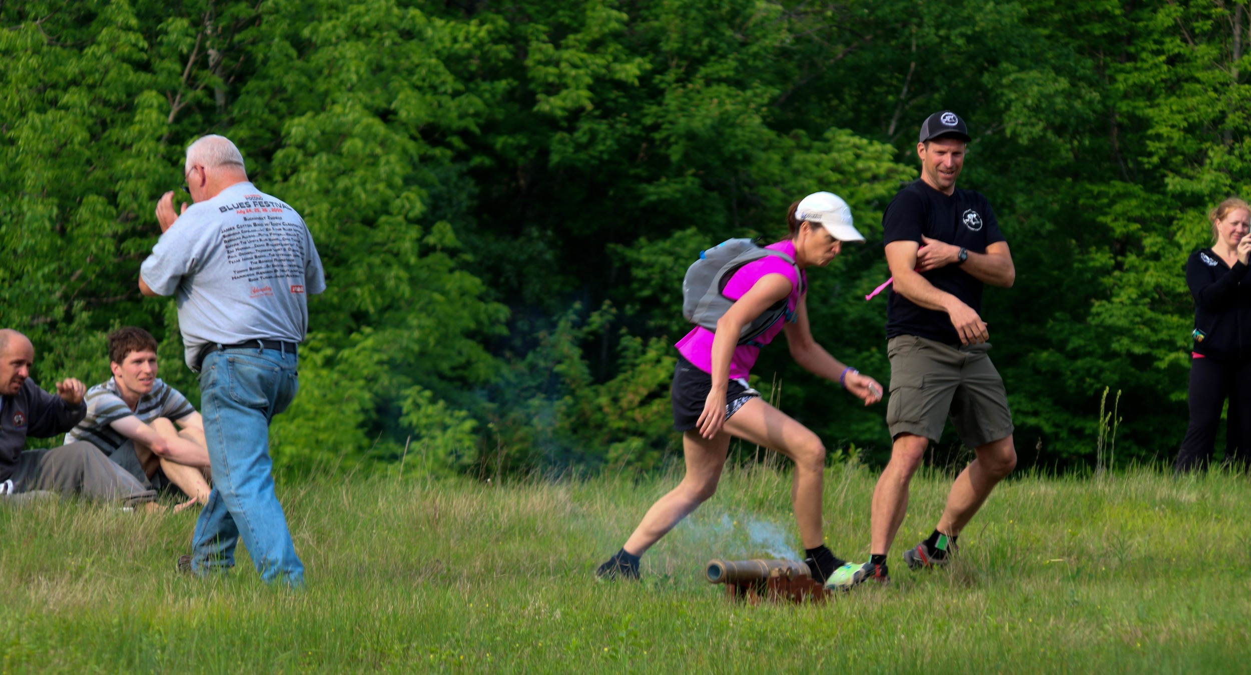 Runner Linda Bahnson and race director Andy Weinberg run from the cannon that was used to start the 88k race.