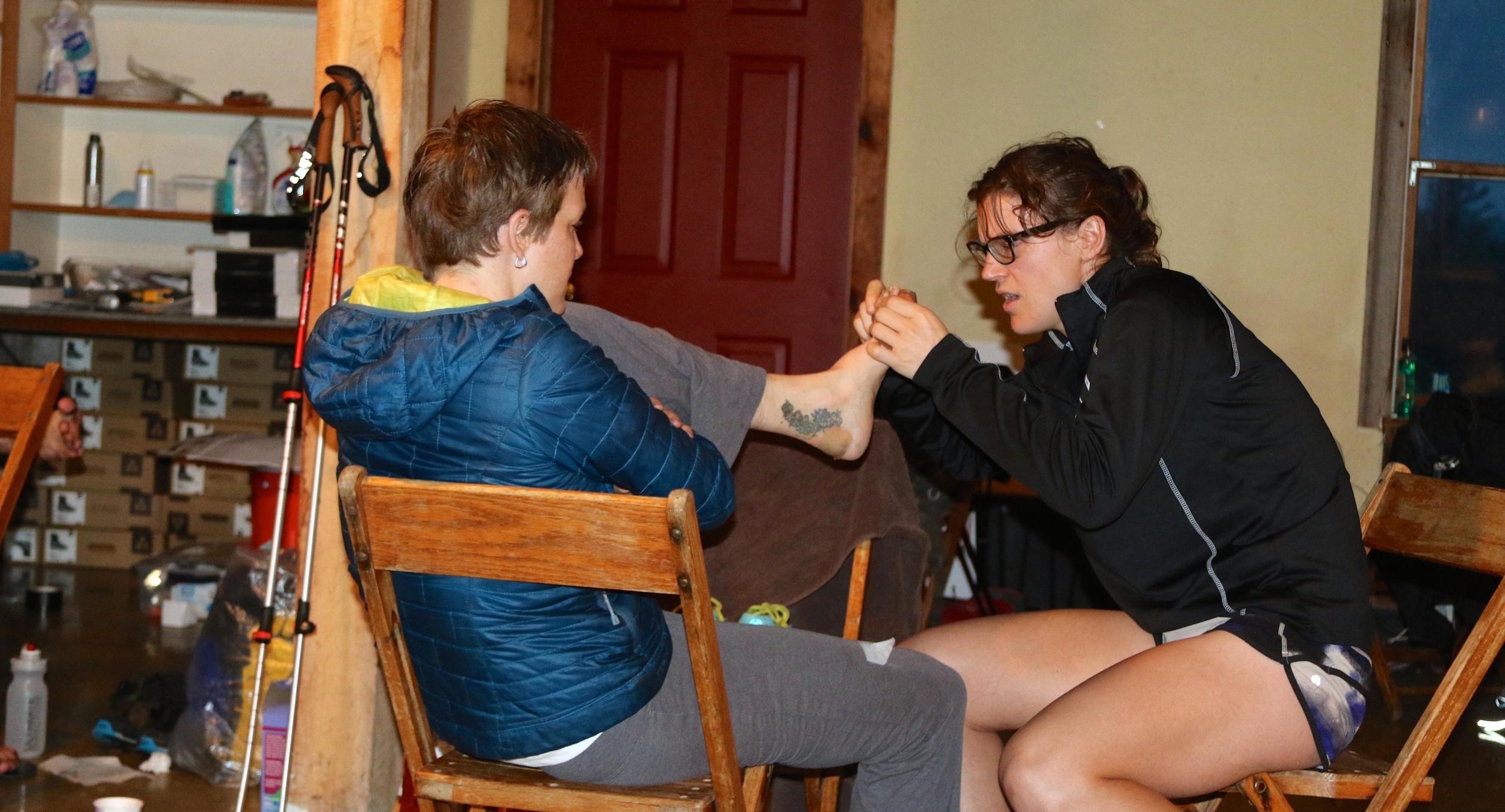 Jordan treats blisters for 88k runner Rebecca Schubert.