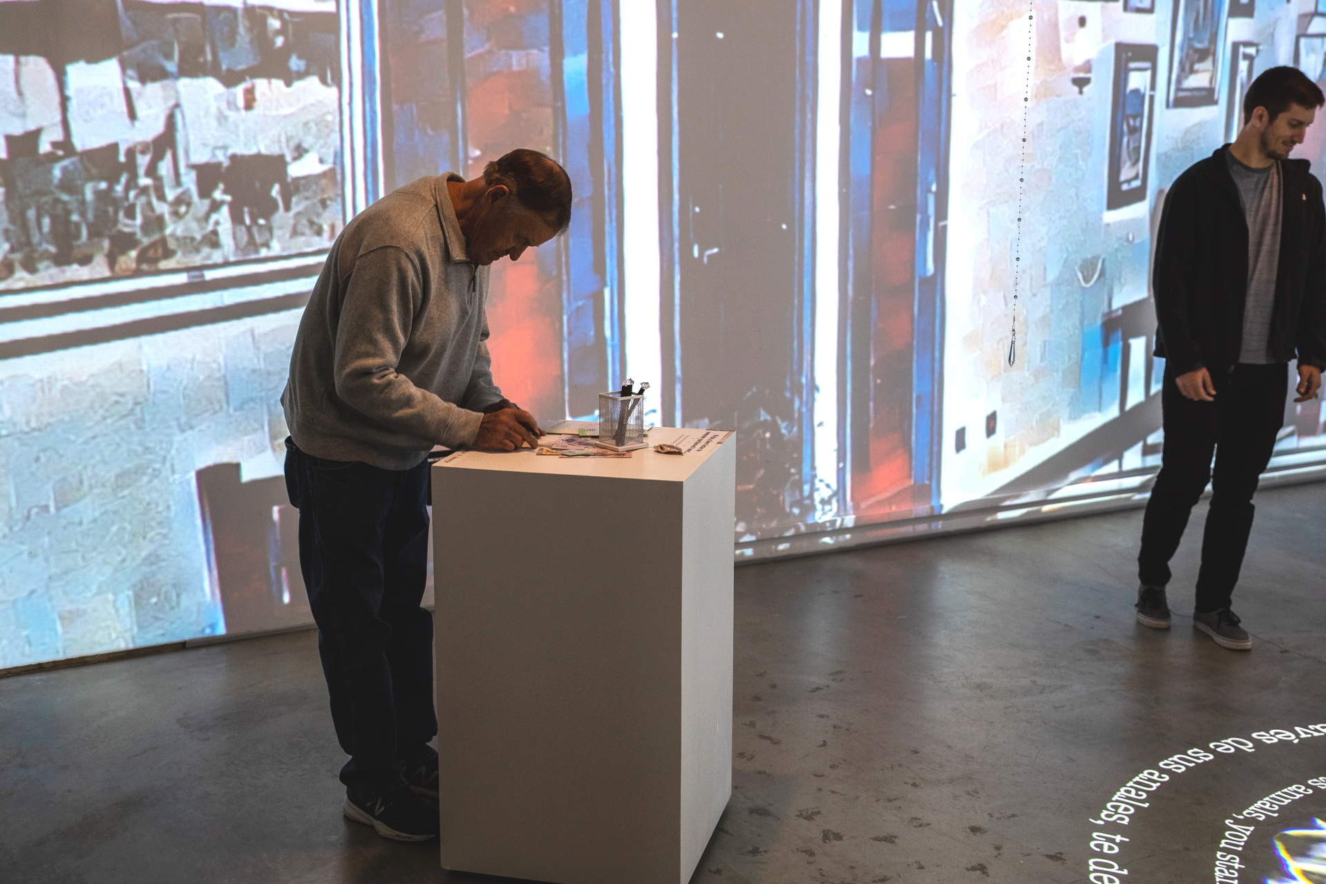A gallery visitor participating in the ritual of writing a love letter
