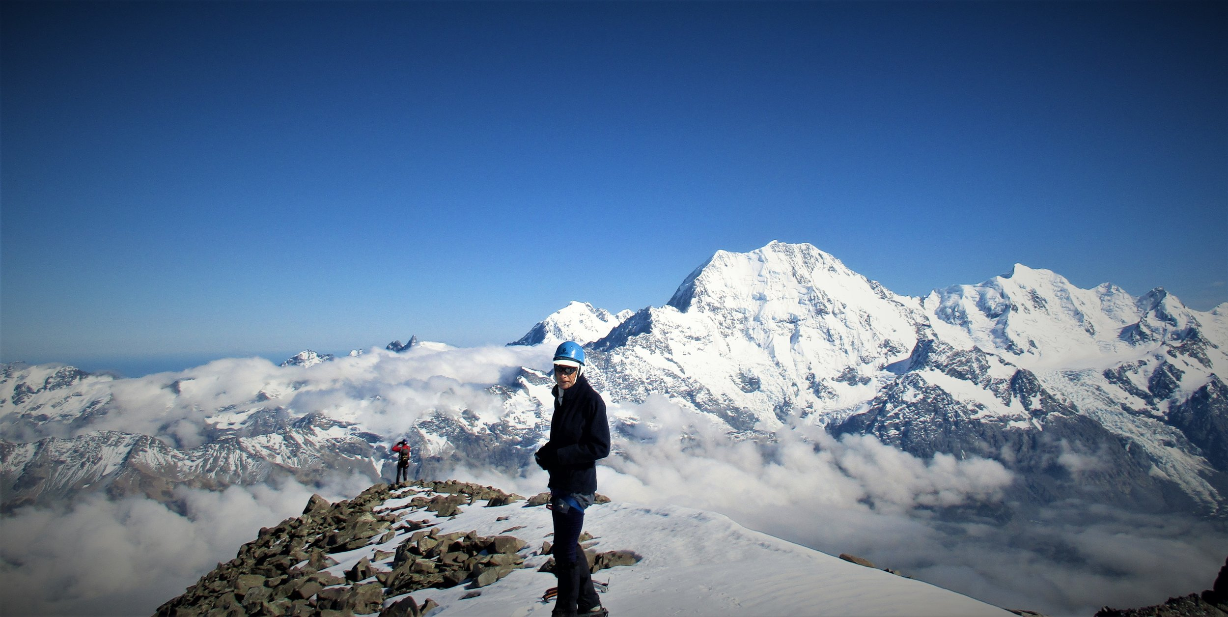 Ben looks into the Camera as George takes in the view of La Perouse, Aoraki,/Mt Cook and Mount Tasman from the large summit of the Nun's Viel.