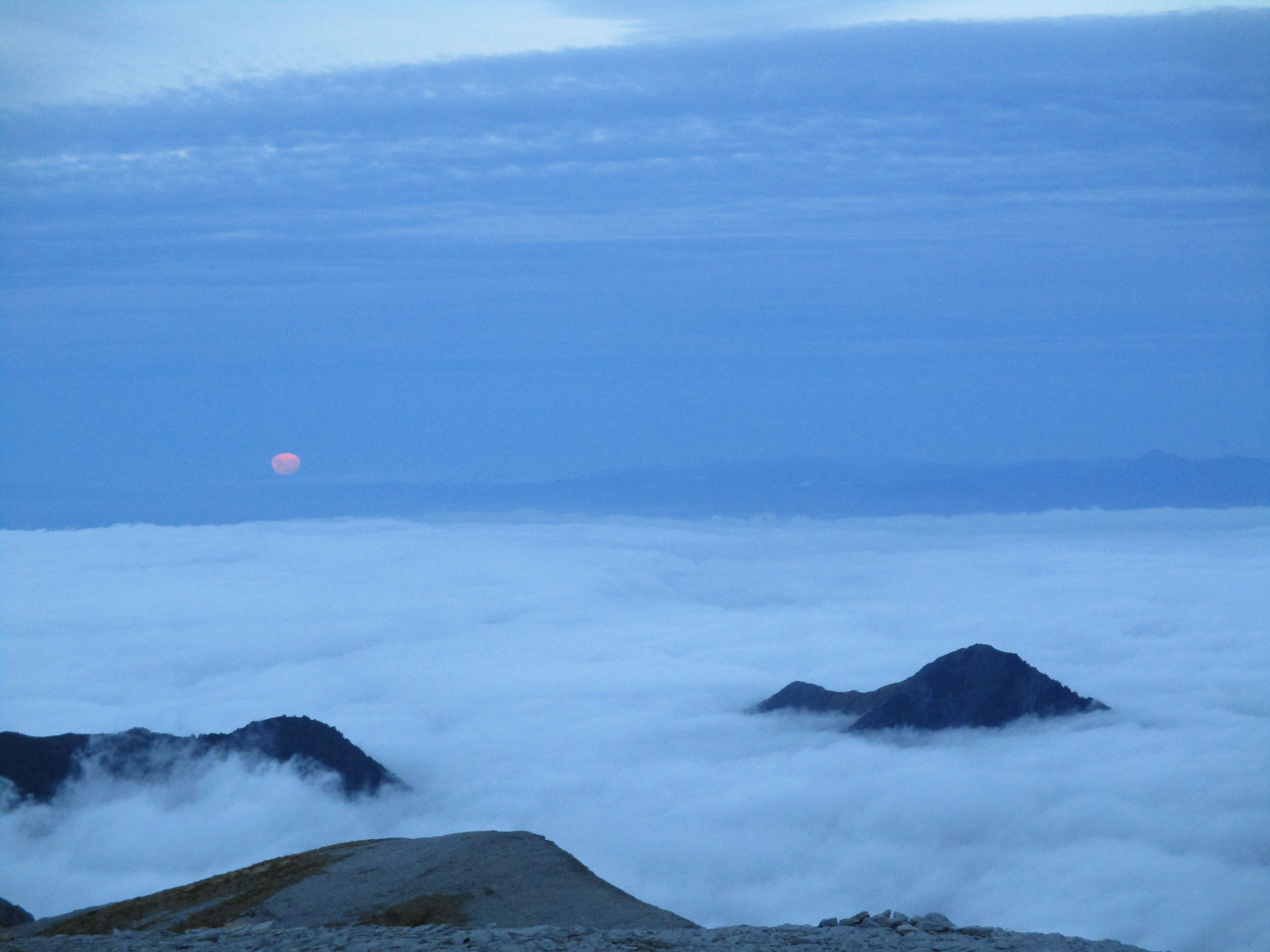 A full moon rising above the clouds.