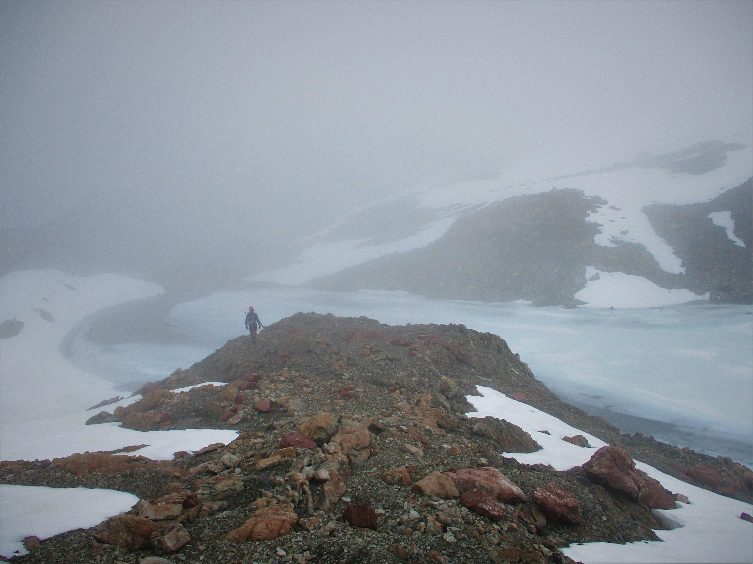 Approaching a semi frozen mountain tarn