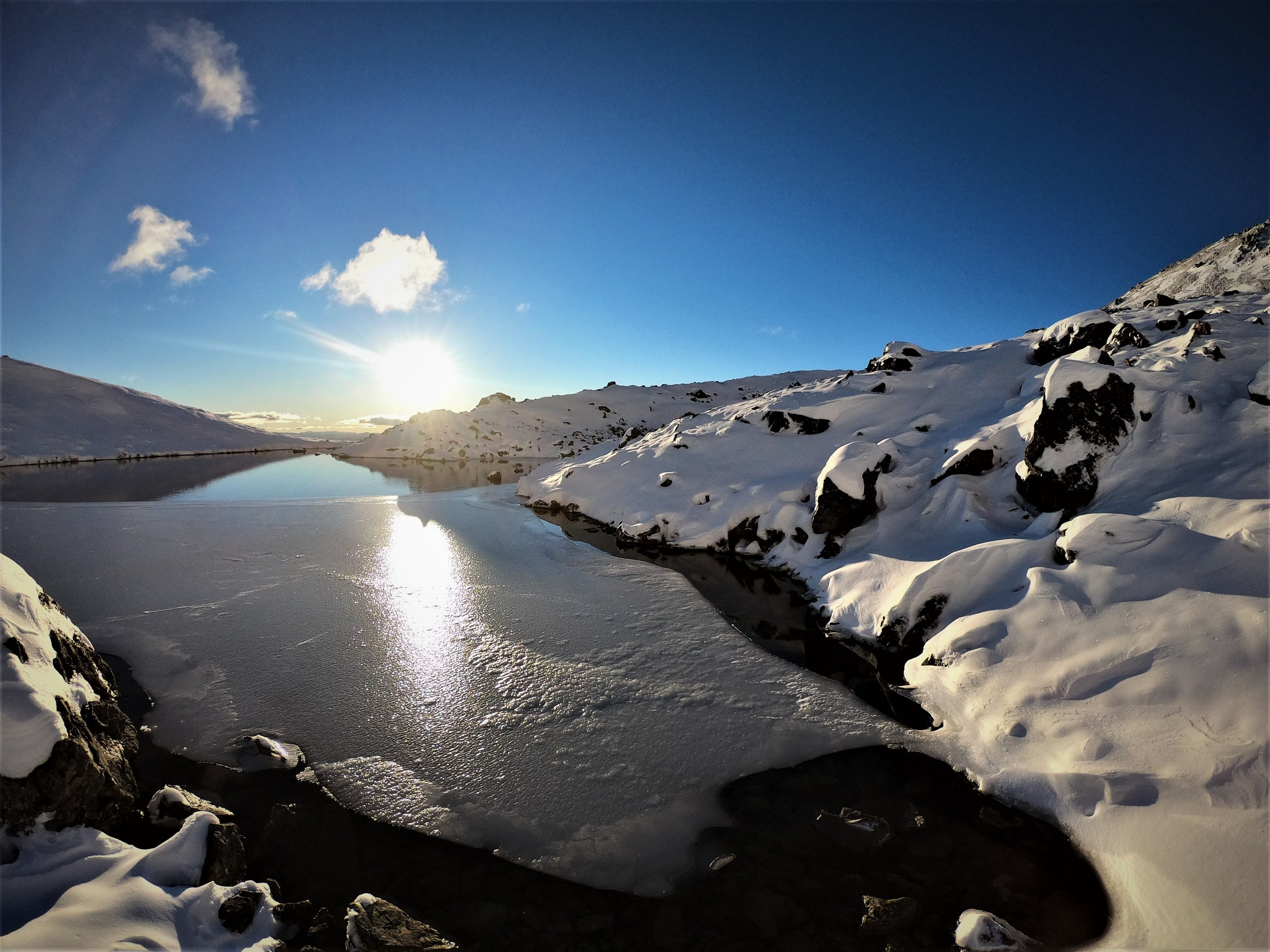 Small mountain tarns begin to freeze over.