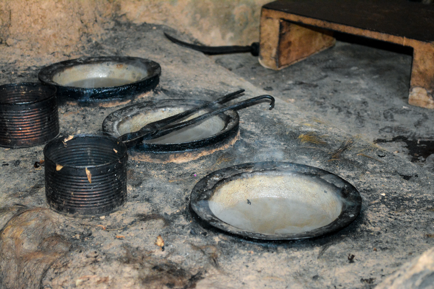 The tops of the cauldrons that are inset in the stove.