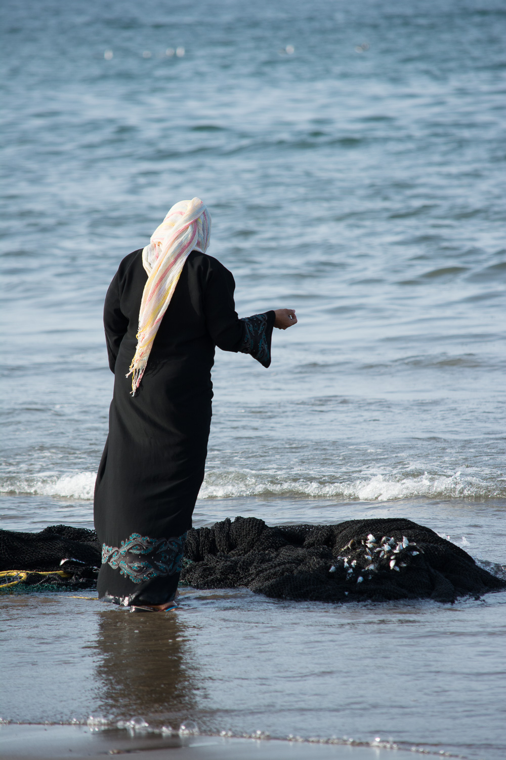 A local mom having negotiated with the fishermen is waiting for her order and looking at the net.