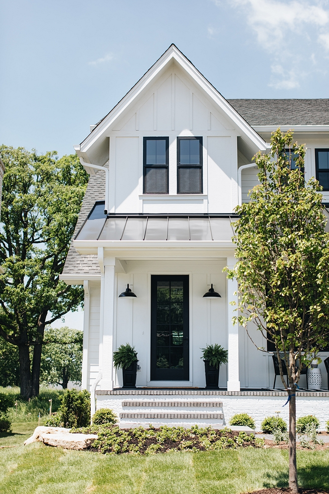 This newly-built white modern farmhouse features white siding black vinyl windows, black metal roof, grey shingle roof and a black front door.