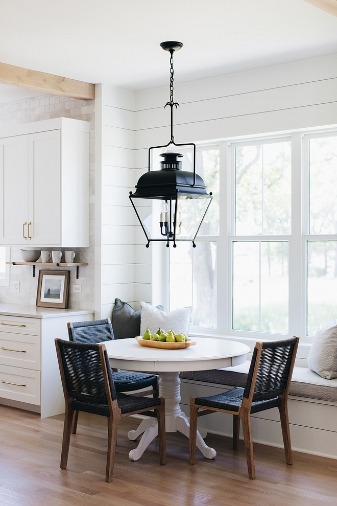 This bright breakfast room features a built-in banquette and custom shiplap paneling.