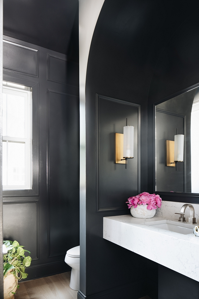 This powder room features black paneled walls, painted in  Benjamin Moore Wrought Iron 2124-10,  and a marble-looking floating vanity. Countertop is  Statuary Nuvo from Caesarstone.   Vanity –  Caesarstone mittered to create a chunky look.