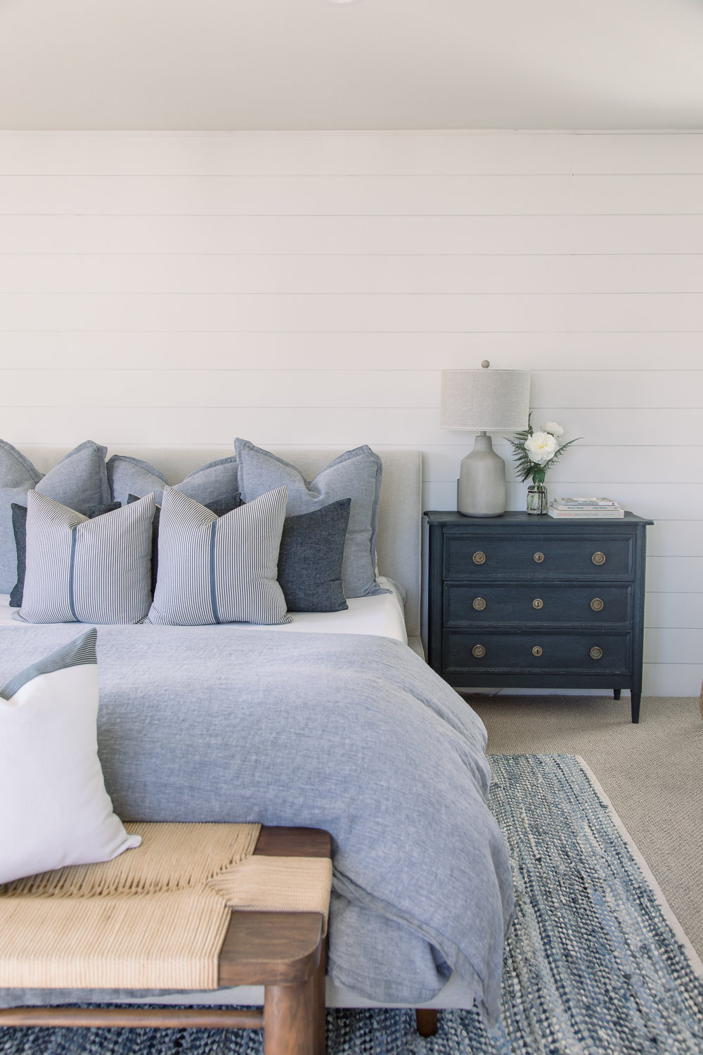 The shiplap wall in the bedroom combined with the cool blue hues sparks dreams of being on a boat.