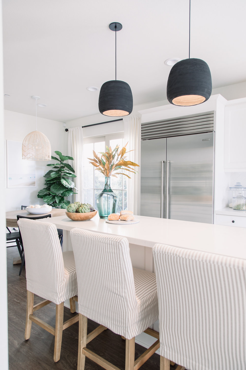 The striped slip-covered bar stools are reminiscent of beach chairs, while the countertops reflect the color of white sand.