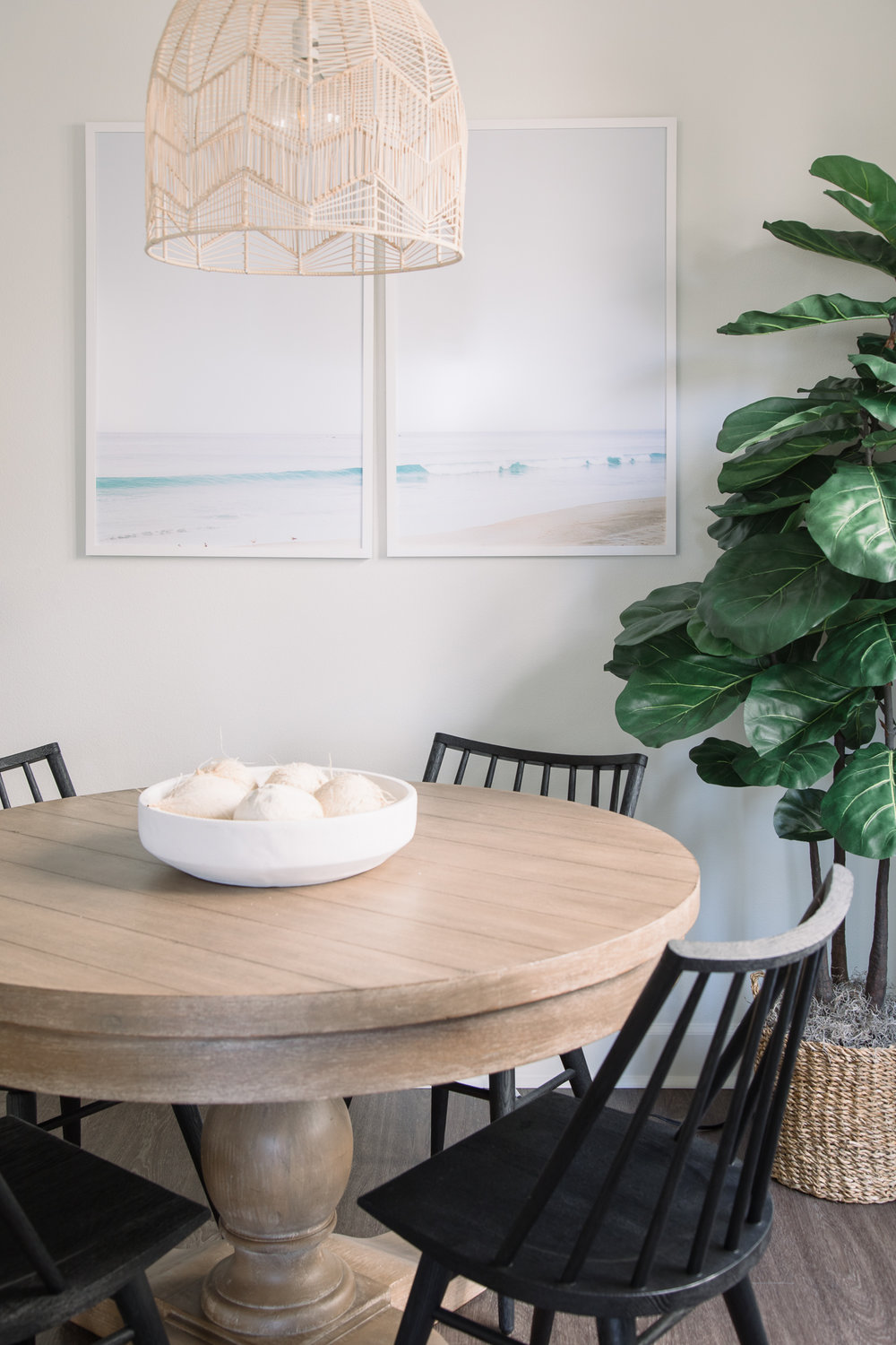 The white pendant light floats dreamlike above the table, anchored by delicate black chairs.