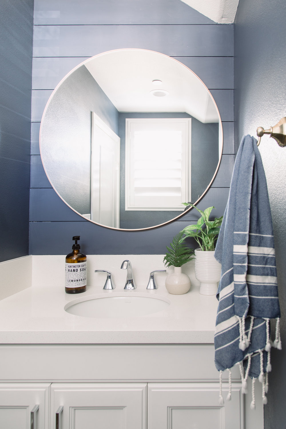 The powder room is painted a deep blue, in stark contrast to the white walls in the rest of the house.