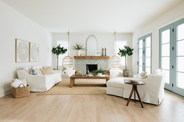 The complete living room. The French doors are a perfect touch of color that carries through the fireplace and connects the indoor with the outdoor. The swing chairs flawlessly frame the fireplace and go nicely with the mantel as well.