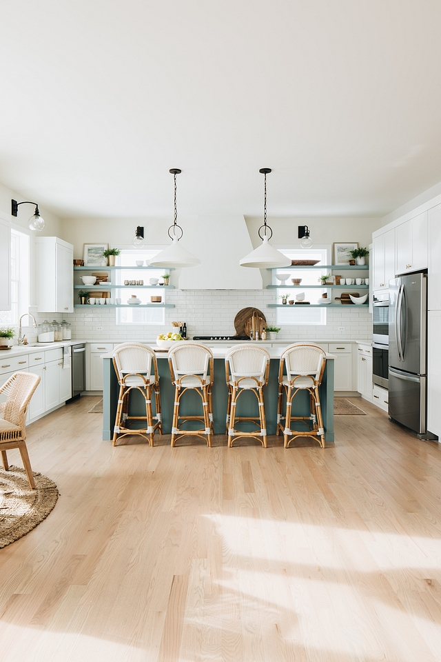 The kitchen keeps the same color scheme as the rest of the house, with a slightly darker shade of aqua on the island, anchoring it a bit and setting it apart from the white of the rest of the kitchen.